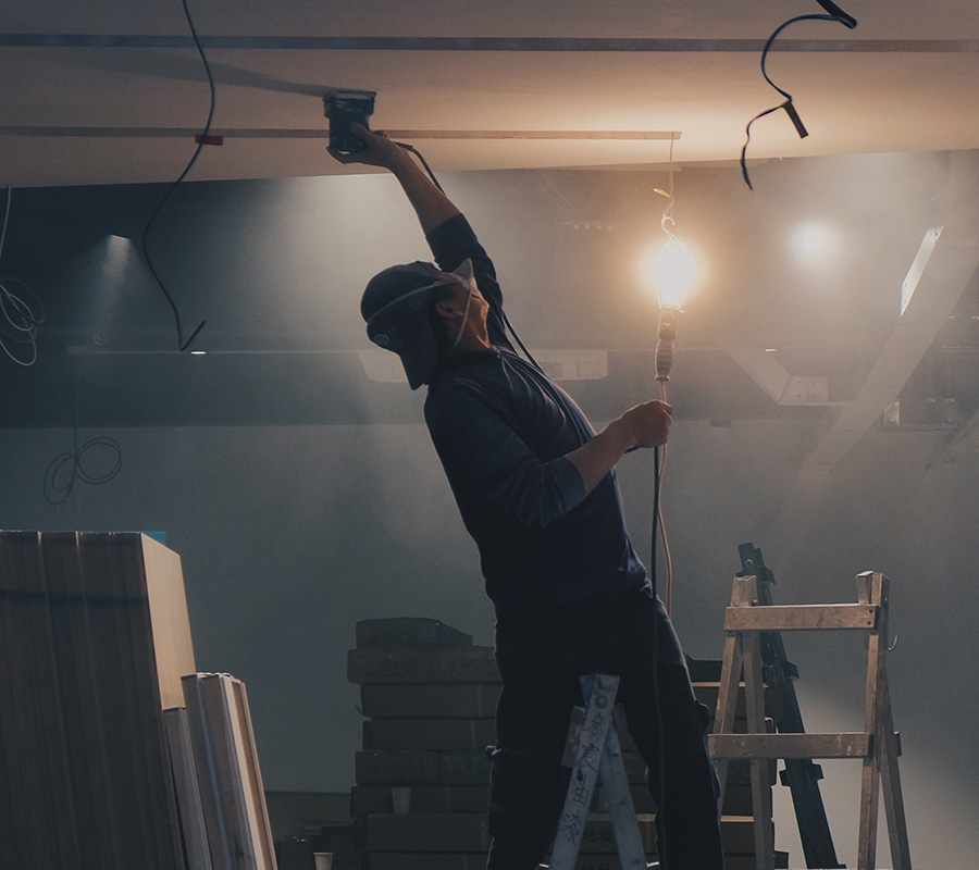 Contractor sanding ceiling with PPE covered by contractor insurance by Insure Smart
